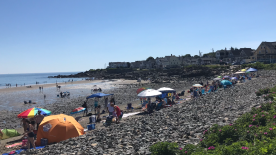 Beach-goers are packed in everywhere on the rocks and on the flats.