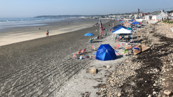 Beach lovers get set up early while the tide is out.